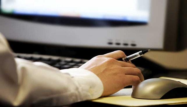 יד מחזיקה עט מול מחשב עם עכבר ומקלדת